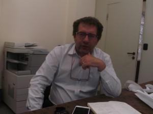 un uomo seduto alla scrivania con la mano sotto il mento