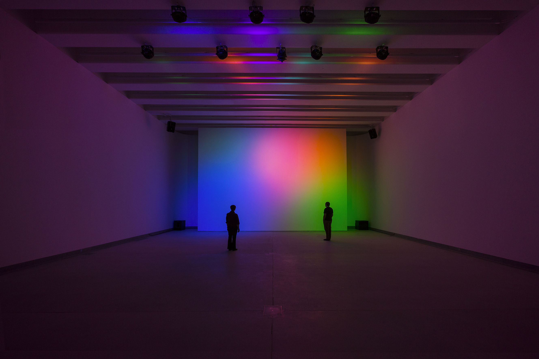 Stanza illuminata con luci di vari colori con due persone all'interno