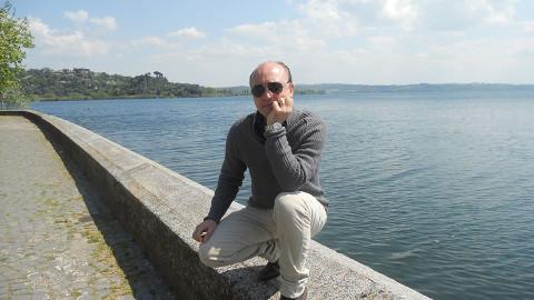 Un uomo seduto su un muretto con alle spalle il mare