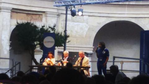 una donna e due uomini seduti a un tavolo su un palco davanti al pubblico