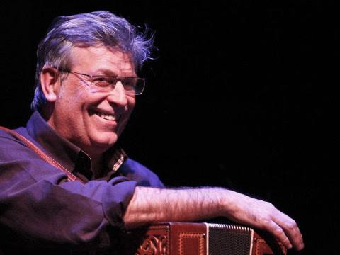 un uomo sorride con la mano poggiata a una fisarmonica