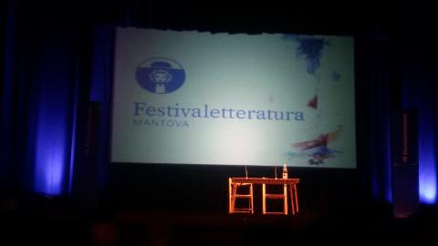 due sedie e un tavolo davanti allo schermo di un cinema con la scritta Festivaletteratura