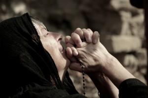 anziana con un velo nero prega tenendo un rosario tra le mani giunte