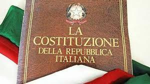 copertina di una stampa della Costituzione poggiata sulla bandiera italiana