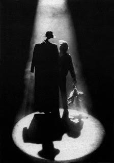 cono di luce che illumina nel buio una persona accanto a un manichino vestito con cappotto e cappello