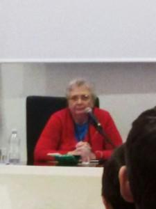 Agnese Moro seduta a un tavolo davanti a un microfono