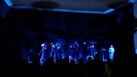 attori in scena con cappotti scuri e ombrelli aperti