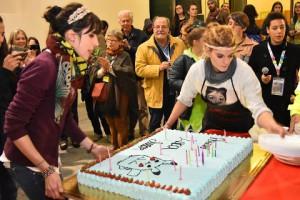due ragazze sistemano su un tavolo una grande torta