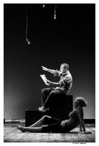 Un uomo seduto su un cubo legge da un foglio mentre una donna sta sdraiata accanto al cubo