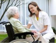 una oss con un'anziana in sedia a rotelle