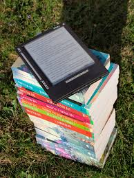 un e-reader sopra una pila di libri cartacei