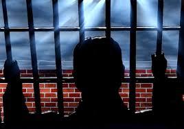 detenuto dietro le sbarre di un carcere